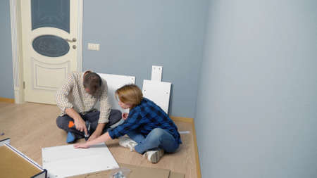 couple man and woman together install furniture in their apartment.