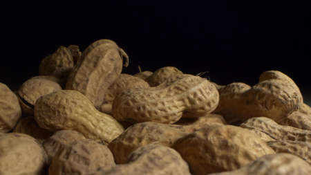 extremely close-up, detailed. peanuts in shells on a dark background