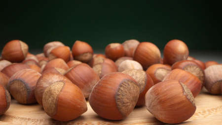 extremely close-up, detailed. many hazelnuts on a dark background. changing lighting from dark to light Фото со стока