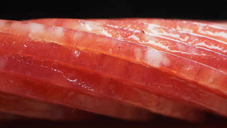 extreme closeup, detailed. salami sausage cut into thin pieces on a wooden board