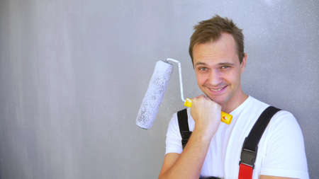 a handsome man in work overalls with a paint roller looking at the camera Zdjęcie Seryjne
