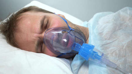 portrait of a man in an oxygen mask who lies on a bed in a hospital