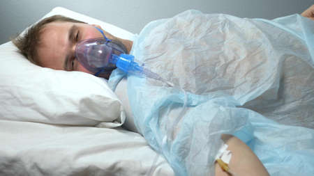vertical. a man in an oxygen mask with a dropper lies on a bed in a hospital