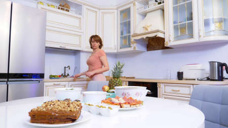 woman in shorts and a T-shirt lays the table at home in the kitchen