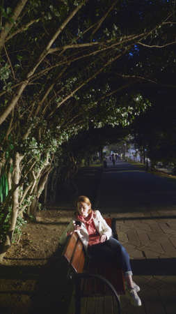 woman in white leather jacket use smartphone while sitting on a park bench