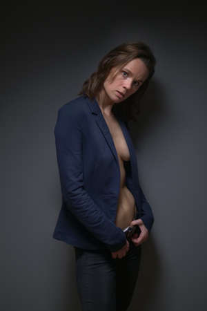 beautiful slender woman in a strict jacket on a naked body. grey background