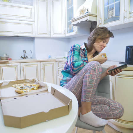 girl using smartphone while sitting at home in her kitchen