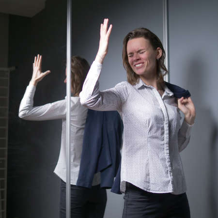 portrait of an emotional business woman taking off her jacket, smiling happily Фото со стока