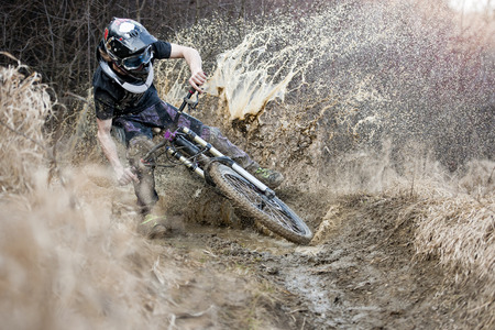 water cycle: Mountainbiker monta en el camino en el barro