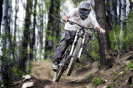 Mountainbiker rides on path in forest Redactioneel