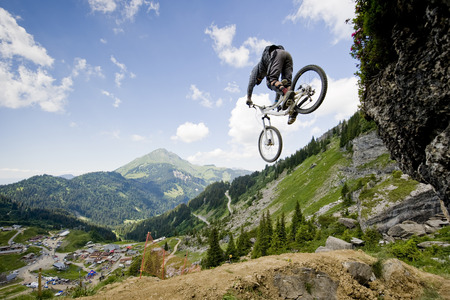 alps: Mountainbiker jumping from a rock
