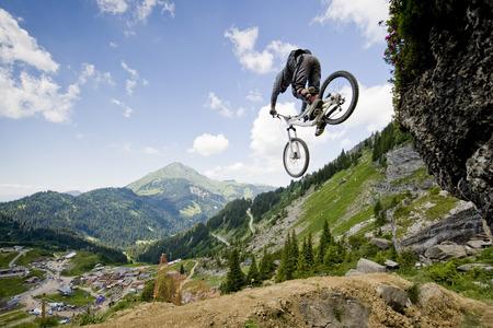 Mountainbiker springen van een rots