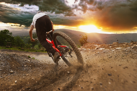 Man on mountain bike rides on the trail on a stormy sunset. Stockfoto