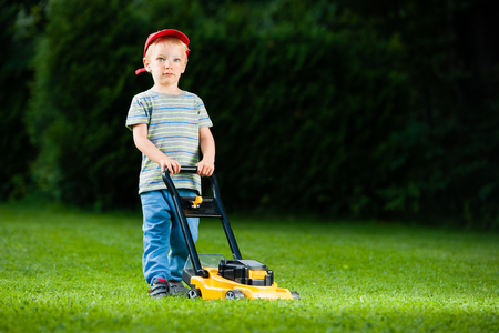 simulations: Cute boy mows lawn by yellow lawn mower Stock Photo