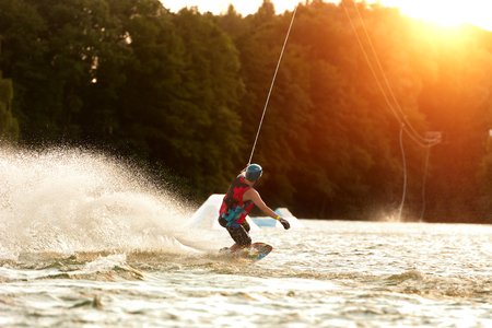 Wakeboarder surfing across a lake 版權商用圖片