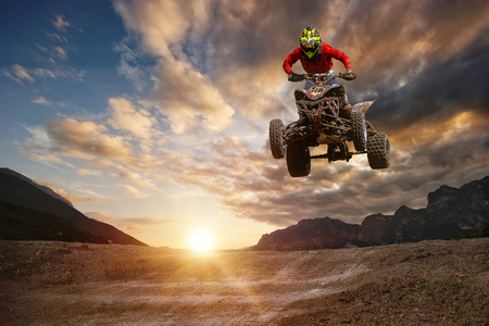 Man on atv jump on the trail during sunset.