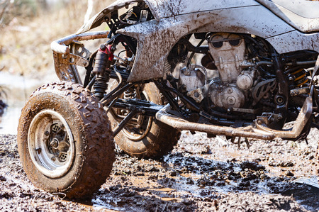 Close-up of dirty atv suspension and angine