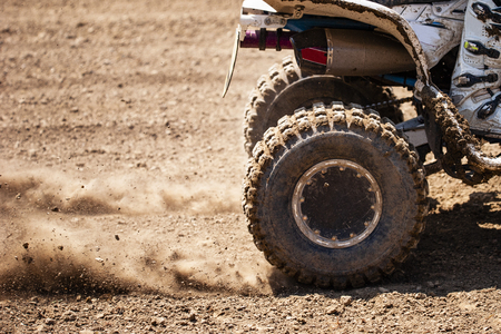 ATV quadbike start in a stony road and having wheel-spin making a spray of debris.