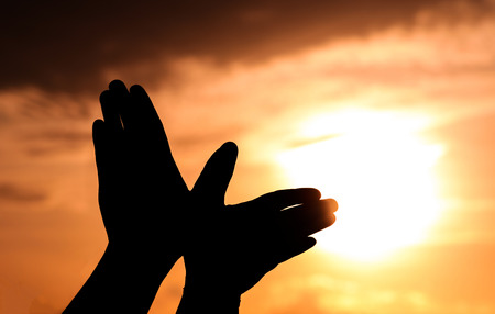 uniting: Hand silhouette under a sunset backdrop Stock Photo