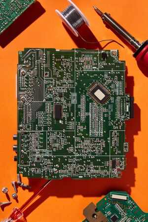 Green circuit board isolated on orange background. Template with a copy space Stock Photo