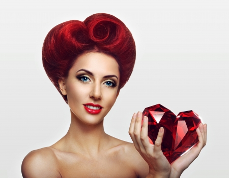 Beautiful ginger lady holding a crystal heart in hands photo