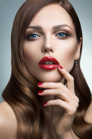 Portrait of beautiful girl with red lips and blue eyes