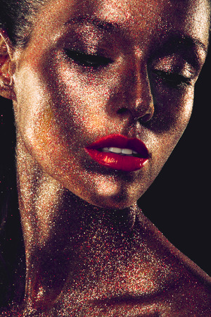 Beautyful girl with gold glitter on her face and red lips photo