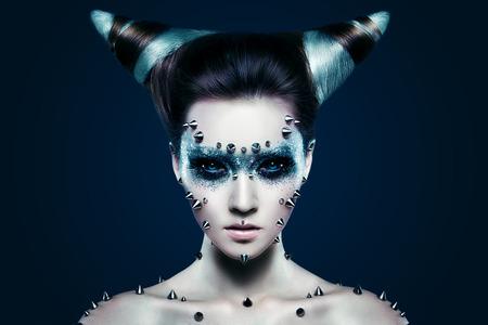 demonio: Muchacha del demonio con los puntos en la cara y el cuerpo. Ojos negros