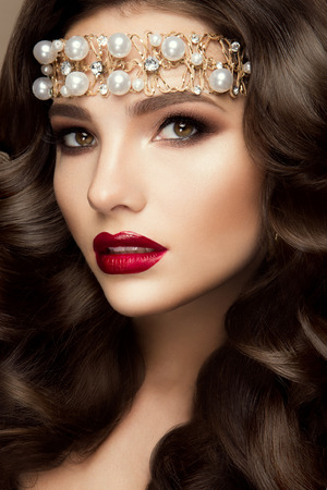 Beautiful young model with red lips and curly hair