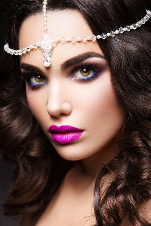 Close-up portrait of beautiful woman with bright make-up and pink lips photo