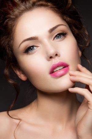 밝은 메이크업과 핑크 입술을 가진 아름 다운 여자의 근접 초상화