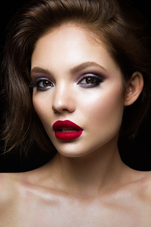 Beautiful young model with red lips and dark makeap