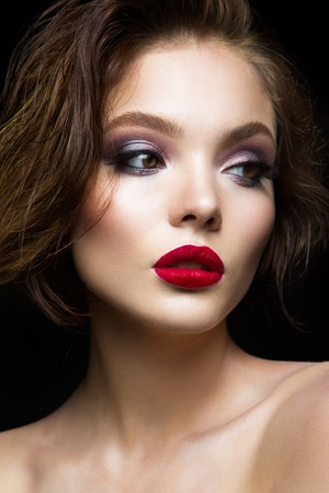 look up: Beautiful young model with red lips and dark makeap