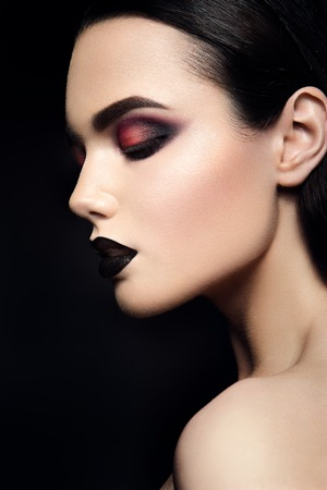 look at: Beauty Fashion Model Girl with Black Make up. Dark Lipstick. Smoky eyes. Stock Photo