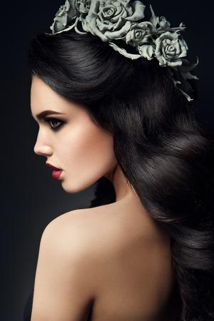 mujer con rosas: Chica belleza de la modelo del retrato con grises Rosas Peinado. Labios Rojos. Hermosa maquillaje de lujo y pelo Foto de archivo