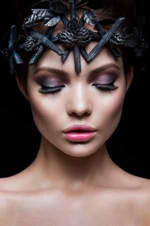 Close-up portrait of beautiful woman with bright make-up. Black accessories.