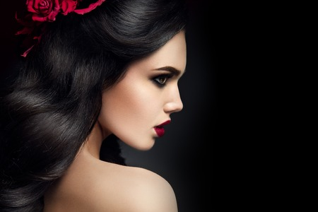 Beauty Fashion Model Girl Portrait with Red Roses Hairstyle. Red Lips. Beautiful Luxury Makeup and Hair Foto de archivo