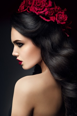 sexy glamour: Beauty Fashion Model Girl Portrait with Red Roses Hairstyle. Red Lips. Beautiful Luxury Makeup and Hair Stock Photo