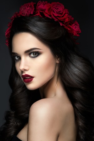 valentines: Beauty Fashion Model Girl Portrait with Red Roses Hairstyle. Red Lips. Beautiful Luxury Makeup and Hair Stock Photo