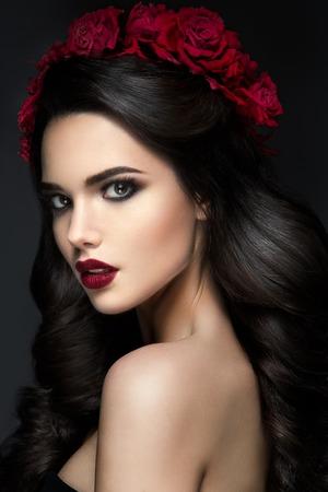 rosas rojas: Chica belleza de la modelo del retrato con Rosas Rojas Peinado. Labios Rojos. Hermosa maquillaje de lujo y pelo