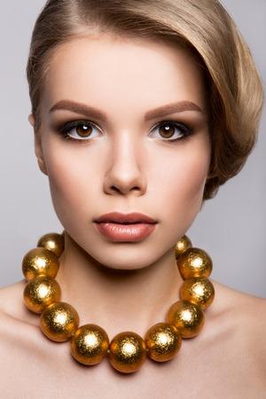 Fashion Model Portrait. Hairstyle, Professional Makeup and False Eyelashes. Gold Make-up