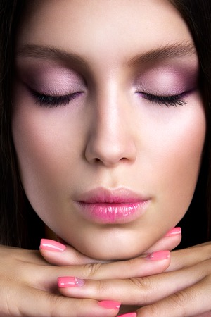 Romantic girl with beautiful makeup. Pink manicure.