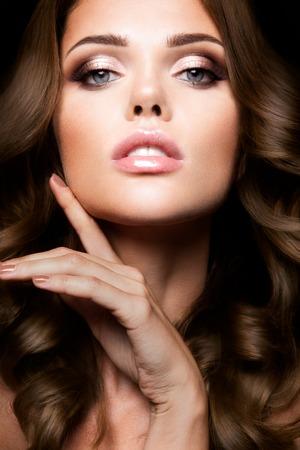 밝은 메이크업과 곱슬 머리를 가진 아름 다운 여자의 근접 초상화
