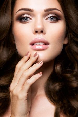 明るい化粧と巻き毛の美しい女性のクローズ アップの肖像画