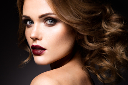 Close-up portrait of beautiful woman with bright make-up and dark red lips Фото со стока