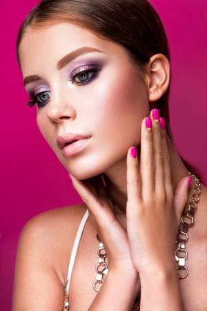 unas largas: Muchacha de la belleza del modelo de manera con el maquillaje brillante, el pelo largo, las uñas cuidadas y joyas de oro. Mujer del encanto aislado sobre fondo rosa estudio.