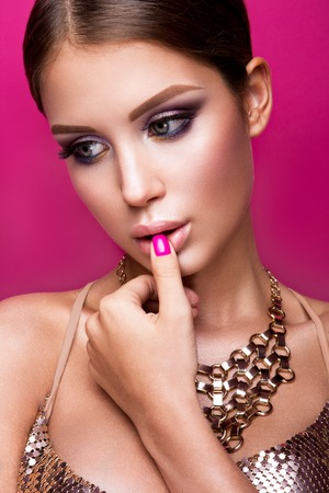nail studio: Beauty fashion model girl with bright makeup, long hair, manicured nails and gold jewelry. Glamour woman isolated on pink studio background.