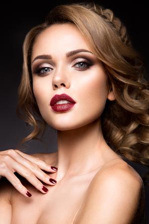 lapiz labial: Close-up retrato de mujer hermosa con maquillaje brillante y labios de color rojo oscuro Foto de archivo