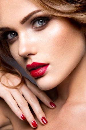 Close-up portrait of beautiful woman with bright make-up and red lips. Stock Photo