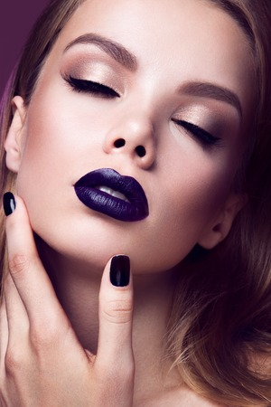 Close-up portrait of beautiful woman with bright make-up and purple lips